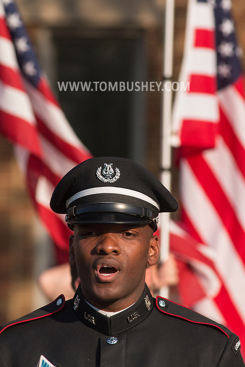 Goshen, New York -  Army Staff Sergeant Jeremy Gaynor, the lead singer in the West Point Band, sings the national anthem at the start of the Orange County Law Enforcement Officer Memorial Service on May 8, 2015, at the entrance of the Orange County Courthouse. The memorial service honors the memory of the members of the Orange County law enforcement community that died in the line of duty. The service also pays tribute the families and loved ones left behind for their courage, dignity and perseverance.
