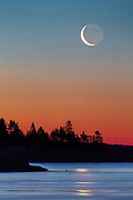 A crescent moon hovers over fir trees on a sloping shoreline with the first light of day creating a beautiful burning red in the sky, while below the flowing waters of the ocean and Kennebec Rivers pass, catching the reflection of the moon.
