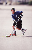 1997:  Beach inline hockey skating. Young boy with green ball on hockey stick skating outdoors with backwards hat.  Lifestyle.  Transparency image scan.