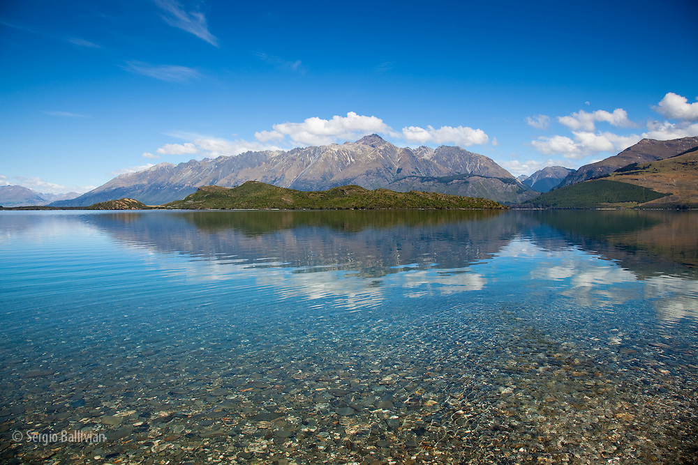 High-noon sun on the  high peaks of the Southern Alps creates mirror-like reflections on Lake Wakatipu near Glenorchy in New Zealand's South Island.