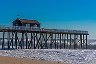 Waves crash against a fishing pier on a bright clear morning. Editorial Use Only.
