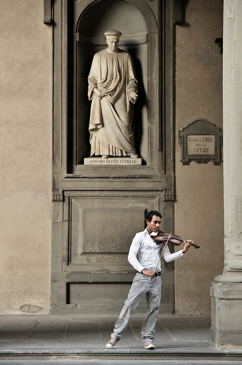 Florence, Italy. Street musician plays classical violin under statue of city father Cosimo de Medici. Outside the Uffizi Gallery