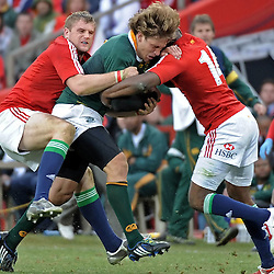 Frans Steyn of the Springboks is tackled by Jamie Heaslip and Ugo Monye of the British and Irish Lions during the British and Irish Lions tour 2009