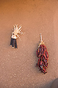 Dried maize and chile peppers hang on an adobe wall at the ancient Native American Taos Pueblo outside Taos, New Mexico. The pueblos are considered to be one of the oldest continuously inhabited communities in the United States and is designated a UNESCO World Heritage Site.