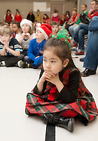 "Nova McLeod along with her fellow Elm Street School students listen as Mr. Johnson recites ""Twas the Night Before Christmas"" before being dismissed for Christmas vacation Friday afternoon.  (Karen Bobotas/for the Laconia Daily Sun)"