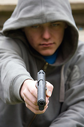 Youth gun crime - 16 year old hoody with ,45 cal automatic pistol; London UK Posed by model