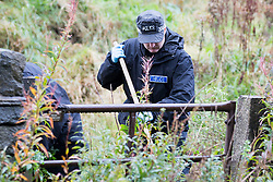 © Licensed to London News Pictures. 11/10/2016. Tintwistle UK.Police search the ground at the scene where a murder investigation has started after a badly burnt body was found in a lay-by on the A628 Woodhead Pass near the village of Tintwistle. The body was found by a member of the public & police are working to discover if the victim was male or female. by Photo credit: Andrew McCaren/LNP