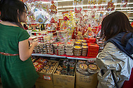 Two women buy nuts and candies at Arcadia Market on Saturday, Feburay 2, 2013 ahead of the Lunar New Year in Los Angeles, California,  This year, the first day of the Year of the Snake, falls on Sunday, Feburary10.  (Photo by Ringo Chiu/PHOTOFORMULA.com).