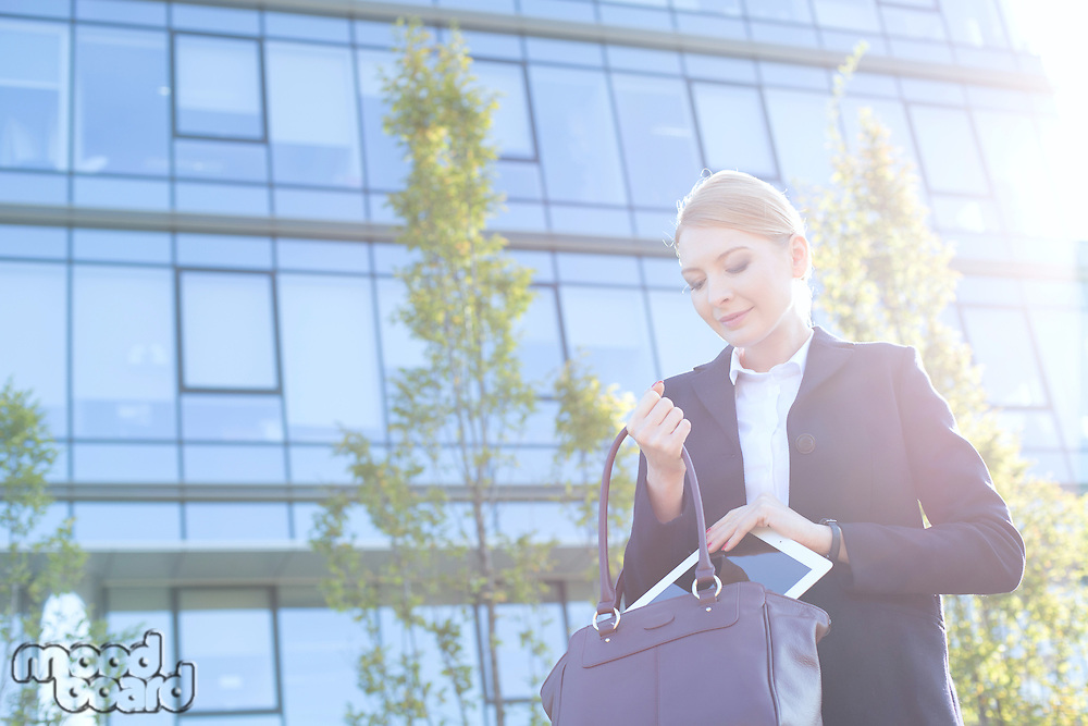 Businesswoman putting digital tablet in purse on sunny day
