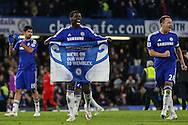 Kurt Zouma of Chelsea (centre) holds up a banners saying 'We're On Our Way to Wembley' after the Capital One Cup Semi Final 2nd Leg match between Chelsea and Liverpool at Stamford Bridge, London, England on 27 January 2015. Photo by David Horn.