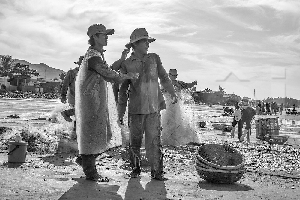 Local fishermen in mid-discussion on the shore of Long Hai Beach, Vung Tau Province, Vietnam, Southeast Asia