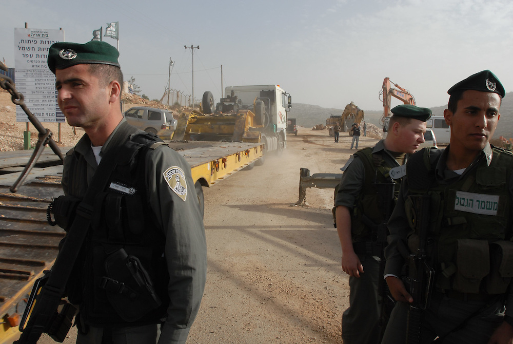 Israeli Border Police soldiers guard a large construction site in Beit Arye settlement, where a new neighborhood was planned to be build. Civil Administration inspectors handed out a warrant to the site manger to stop construction in the site, following Israeli government decision to freeze construction in West Bank settlements for 10 months.