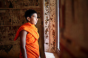 A Buddhist monk watches the world from a once decorative window in the Kataluwa Purvarama Mahavihara temple in Sri Lanka..The temple was originally built in the 13th century and is renowned for its remarkable Kandyan-style paintings in the main shrine, dating from the late nineteenth century. Paintings of Queen Victoria & the Queen Mother too are done in gratitude of Queen Victoria's role in ensuring the free practice of Buddhism outlined in the Kandyan capitulation of Sri Lanka in 1815.