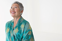Senior woman in dressing gown in studio half length