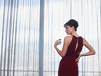 Woman wearing elegant dress looking out of window indoors