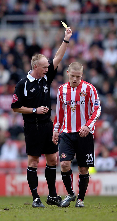 Photo: Jed Wee.<br />Sunderland v Blackburn Rovers. The Barclays Premiership. 25/03/2006.<br /><br />Referee Peter Walton (L) shows Sunderland's Grant Leadbitter the yellow card.