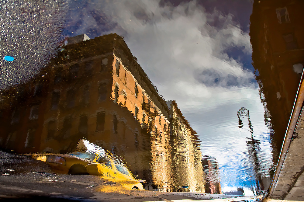 Reflection of a taxi in a puddle on a street of the Lower East Side of Manhattan, New York