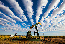 Pump jack in West Texas with 'street rows' cloud formation and wind turbines on the horizon.