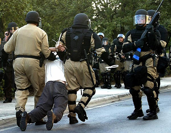 An unidentified protester is dragged away by police after being arrested during a rally against the Free Trade Area of the Americas (FTAA) meetings in downtown Miami, Florida 21 November 2003. Thousands of protesters demonstrated the meetings in Miami.  EPA/Andrew GOMBERT
