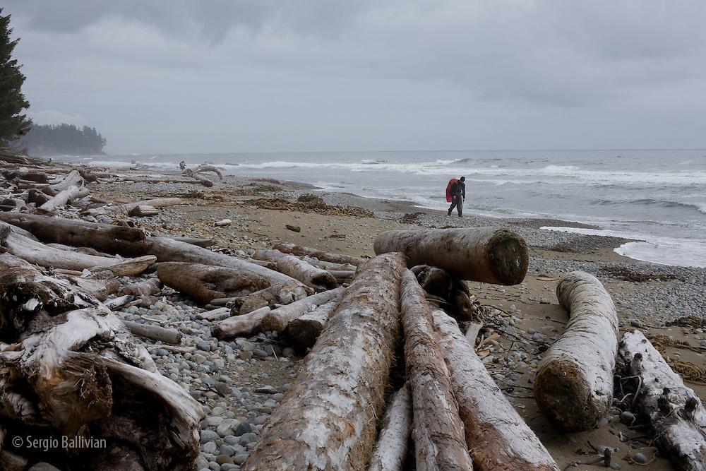 West Coast Trail - Day 2. A solo hiker navigates the coastline as a storm brews in the background.