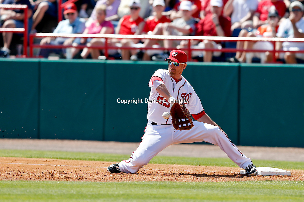 Mar 8, 2013; Melbourne, FL, USA; Washington Nationals first baseman Adam LaRoche (25) catches the ball on a hop for an out against the St. Louis Cardinals during the top of the second inning of a spring training game at Space Coast Stadium. Mandatory Credit: Derick E. Hingle-USA TODAY Sports