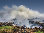 17 MARCH 2014 - PHRAEKSA, SAMUT PRAKAN, THAILAND:  Smoke billows up from a fire burning in the landfill in Samut Prakan. A fire apparently spontaneously started in the landfill in Samut Prakan over the weekend and threatens the homes of workers who live near the landfill. The fire Officials said the fire started when garbage in the landfill burst into flames and the flames were spread by hot, dry winds. Hundreds of people have been evacuated because of the fire and acrid smoke from the fire has spread as far as Bangkok. It hasn't rained in central Thailand in more than three months, impacting agriculture and domestic water use. Many farms are running short of irrigration water and salt water from the Gulf of Siam has come up the Chao Phraya River and infiltrated the water plants in Pathum Thani province that serve Bangkok.  PHOTO BY JACK KURTZ