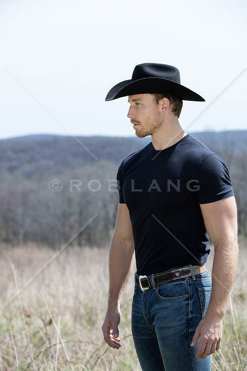 profile of a muscular cowboy outdoors