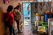 Women in Iztapalapa survey the amount of water that has been delivered to their home, after having used every empty vessel available. It is not uncommon for weeks to pass between water resupply.
