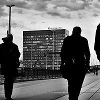 People walk along the bridge over the Rhine, after leaving Novatis Campus, headquarters to the phramaceutical giant,  a gated village within the city, including buildings by star architects. The company also occupies the building visible which is on the far side of the river.<br /> <br /> Basel, straddling the Rhine, and bordering both Germany and France, is a global centre for the pharmaceutical  industry &ndash; &lsquo;big pharma&rsquo;, with hundreds of biotech and &lsquo;life sciences&rsquo; companies ranging from start-ups to two of the top five global companies: Novatis and Hoffmann La Roche.<br /> <br /> The industry provides roughly 40% of total Swiss exports. The chemical and pharmaceutical industry currently employs around 65,000 people in Switzerland and over 355,000 internationally.