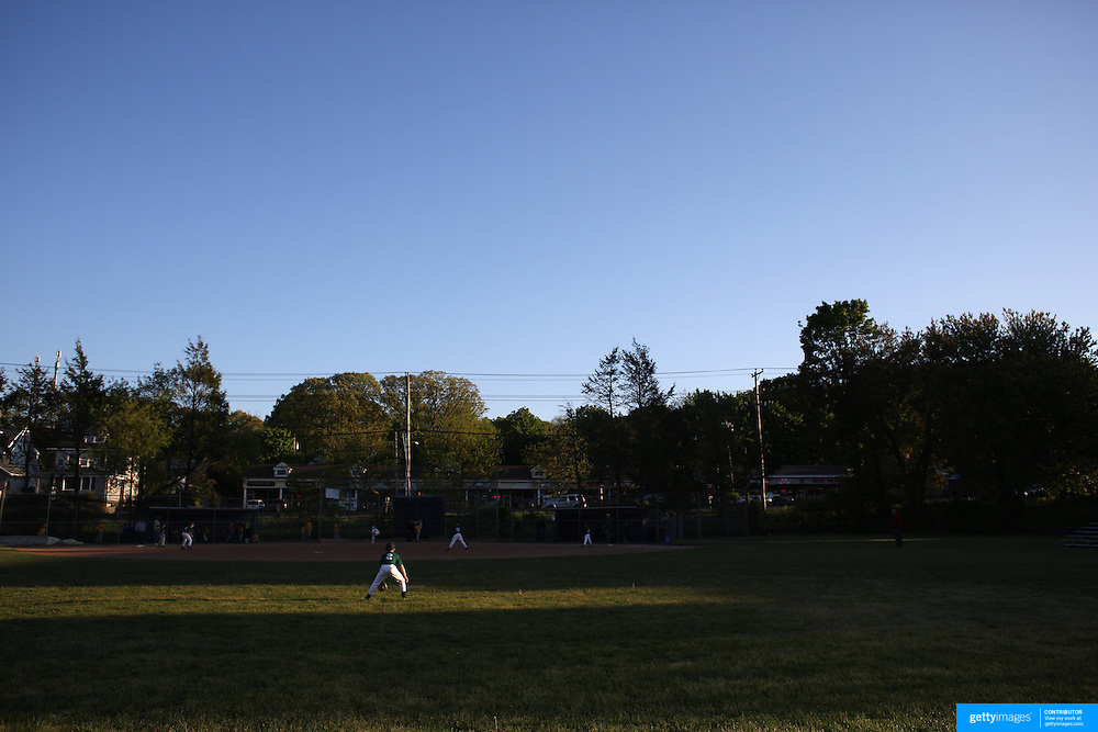 A young baseball player in the outfield during the late afternoon sunlight during the Norwalk Little League baseball competition at Broad River Fields,  Norwalk, Connecticut. USA. Photo Tim Clayton