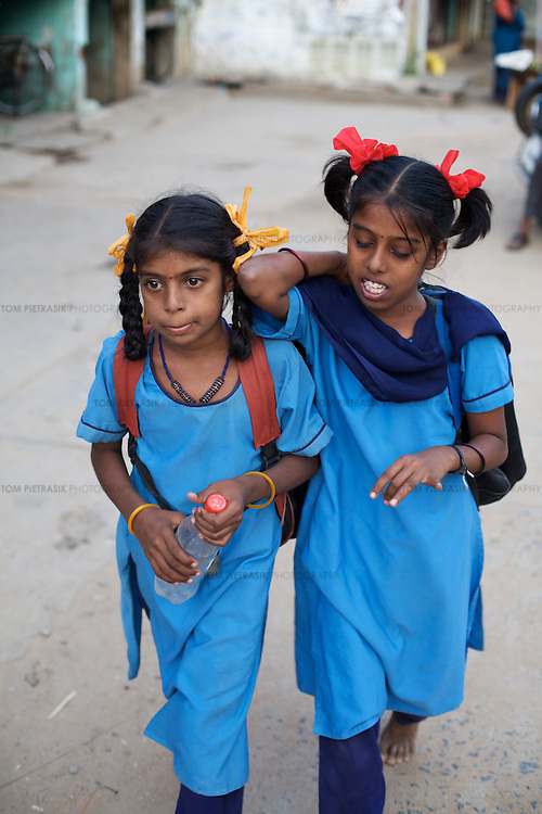 "Vijita (right) and Vijyashree Viswanathan head home to their fishing village after a day at the Government Girls High School, Venugopalapuram, Cuddalore...Vijita (age 14) and Vijyashree (age 11) Viswanathan lost their mother and brother to the tsunami in 2004. They continue to live in the fishing village of Thazanguda with their father Viswanathan, his second wife Kayalvizhi and their two children Sanjay (age 3) and Monica (age 1). ..Until the beginning of the 2009 academic year in June, Vijita and Vijyashree attended the local Thazanguda school. This village school teaches pupils only until the 8th Standard and with Vijita now entering the 9th, it was decided that the two daughters remain together and both travel 3km to the local town school: the Government Girls High School, Venugopalapuram in Cuddalore. ..At the same time Viswanathan decided he would cease day-to-day care of his daughters and place them in the Government Home for Tsunami Children, also in Cuddalore. This was not a move welcomed by either Vijita or Vijyashree and one afternoon after just two weeks at the orphanage, the two girls ran away. At roll call in the orphanage that evening the alarm was sounded and the two sisters were eventually located in Thazanguda waiting for their father and Kayalvizhi who were both away at the time. Realising his daughters' unhappiness, Viswanathan then took them out of the Government home. ..According to her class teacher, Vijita often compares her step-mother to her mother and concludes that she wants her mother back. Vijita confides in her teachers that her stepmother is forever demanding that she and her sister Vijyashree undertake housework. This frustration at home is tempered by the genuine love both sisters have for their father and two younger siblings Sanjay and Monica. Vijita expresses a lonelyness without her mother. Vijita's class teacher Pushpavalli concludes that ""Vijita wants something else beyond the love of her father and sister"". ..Viswanathan appe"