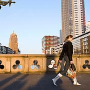 Nederland Rotterdam 21-03-2009 20090321Foto: David Rozing ..Rotterdam centrum, wijnhaven kwartier, vrouw loopt over statige brug, regentessebrug,  met op de achtergrond hoogbouw flats. Gedecoreerde koperen lantaarns verfraaien de brug. wijnhaven wijnhaveneilandCity view Rotterdam, highrising buildings, sunny day. Foto: David Rozing
