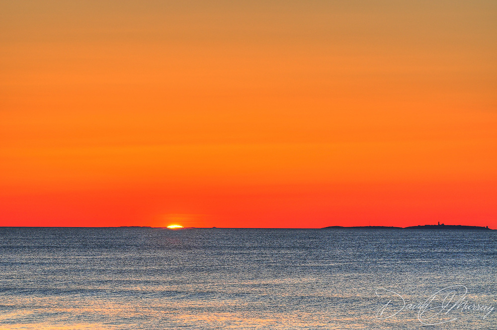 The sun rises behind the Isles of Shoals off Portsmouth, NH