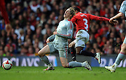 Fernando Torres of Liverpool is tackled by Patrice Evra of Manchester United during the Barclays Premier League match between Manchester United and Liverpool at Old Trafford on March 14, 2009 in Manchester, England.