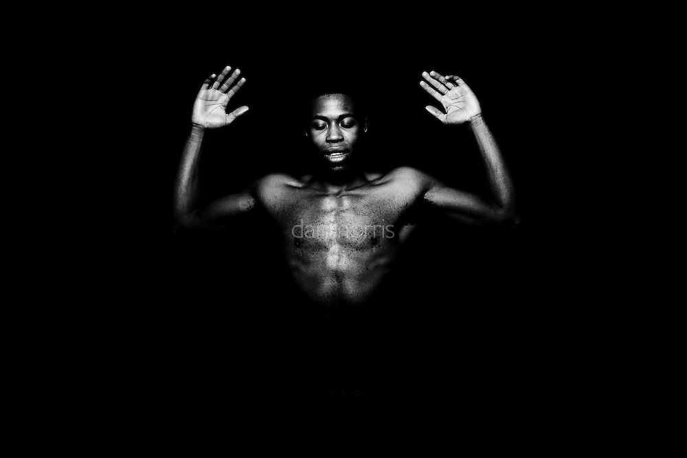 Portrait of young African American man dancing with black backdrop