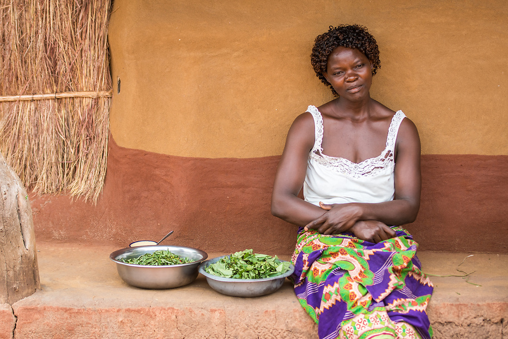 Zambian woman sits next to two bowls of fresh greens that she just prepared, Mukuni Village, Zambia