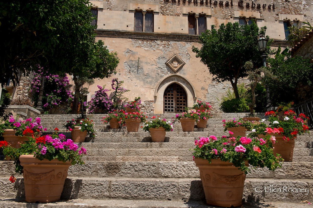 Colourful pots of geraniums on steps in Taormina, Sicily, Italy