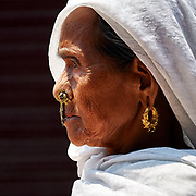 Nepalese woman wearing her golden jewellery while walking around Buddha stupa in Bodanath, Kathmandu, Nepal