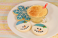 Closeup of snowflake Christmas sugar cookie and two smiling snowmen cookies arranged on a white plate with a small glass of egg nog with candy cane swizzle stick.