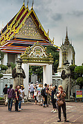 26 NOVEMBER 2012 - BANGKOK, THAILAND: Tourists outside the hall housing the Reclining Buddha at Wat Pho in Bangkok. Thailand's Temple of the Reclining Buddha has gained further global prominence following a 45-minute tour by U.S. President Barack Obama and Secretary of State Hillary Clinton during their November 18-19 visit to the kingdom. Known also as the Temple of the Reclining Buddha, its official name is Wat Phra Chettuphon Wimon Mangkhlaram Ratchaworamahawihan. The temple is also known as the birthplace of traditional Thai massage. There is a popular massage school on the temple grounds.     PHOTO BY JACK KURTZ