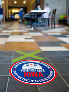 02 JUNE 2020 - WEST DES MOINES, IOWA: Social distancing reminder and spot on the floor at a polling place on primary election day at Valley High School in West Des Moines. Because of the Coronavirus pandemic, all of the polling places in West Des Moines were consolidated to Valley High School, where voting booths were set up with social distancing in mind and booths were sanitized before they were reused. Although Iowa uses a caucus system to select presidential candidates, they use a primary election to select candidates for other offices. Statewide, the most watched race Tuesday is the Democratic Senate primary to select a candidate to run against Republican incumbent Joni Ernst.      PHOTO BY JACK KURTZ