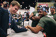 Edward Mumford, 24, right, from a group called Gen Opp, arm wrestles student Samuel Hill during day two of the Conservative Political Action Conference (CPAC) at the Gaylord National Resort & Convention Center in National Harbor, Md.