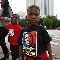 "A young boys is seen with a Barack Obama Hope shirt, as protesters march and hold signs in the No Justice No Peace- ""March Against Gun Violence""  walk from Lake Eola in downtown Orlando, to the Orange County Courthouse on Wednesday, July 17, 2013. The march was organized by the Modarres Law Firm and Orlando attorney Natalie Jackson, one of the attorneys for Trayvon Martins parents. (AP Photo/Alex Menendez)"