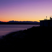 West Point Lighthouse and Olympic Mountain Range behind Puget Sound at sunset, Seattle, Washington USA