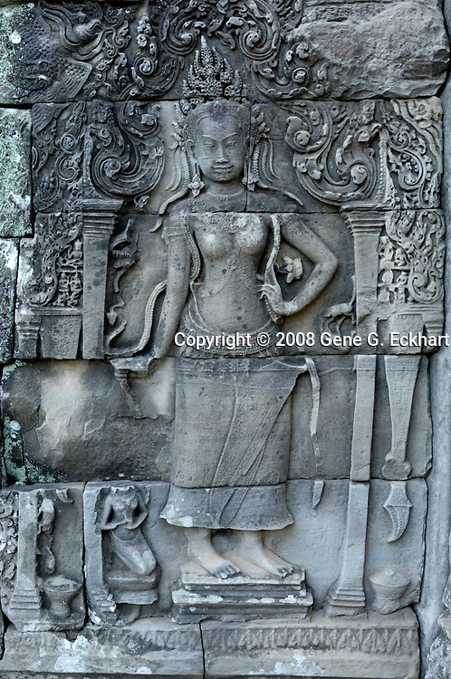 Much like the walls of Angkor Wat, there are many bas reliefs carved into the walls of the temple at Angkor Thom.  Many of the bas reliefs depict stories or events. It really makes the mind wander as you walk through the temple complex and take in all of the magnificent carvings. This temple complex is particularly compelling with giant faces carved out of sheer rock throughout the temple.<br /> <br /> Angkor Thom (Khmer: អង្គរធំ; literally: &quot;Great City&quot;), located in present day Cambodia, was the last and most enduring capital city of the Khmer empire. It was established in the late twelfth century by King Jayavarman VII. It covers an area of 9 km&sup2;, within which are located several monuments from earlier eras as well as those established by Jayavarman and his successors. At the centre of the city is Jayavarman's state temple, the Bayon, with the other major sites clustered around the Victory Square immediately to the north.<br /> <br /> Angkor Thom was established as the capital of Jayavarman VII's empire, and was the centre of his massive building programme. One inscription found in the city refers to Jayavarman as the groom and the city as his bride.<br /> <br /> Angkor Thom seems not to be the first Khmer capital on the site, however. Yasodharapura, dating from three centuries earlier, was centred slightly further northwest, and Angkor Thom overlapped parts of it. The most notable earlier temples within the city are the former state temple of Baphuon, and Phimeanakas, which was incorporated into the Royal Palace. The Khmers did not draw any clear distinctions between Angkor Thom and Yashodharapura: even in the fourteenth century an inscription used the earlier name. The name of Angkor Thom&mdash;great city&mdash;was in use from the 16th century.<br /> <br /> Faces on Prasat Bayon<br /> The last temple known to have been constructed in Angkor Thom was Mangalartha, which was dedicated in 1295. Thereafter the existing structures continued to be modifi