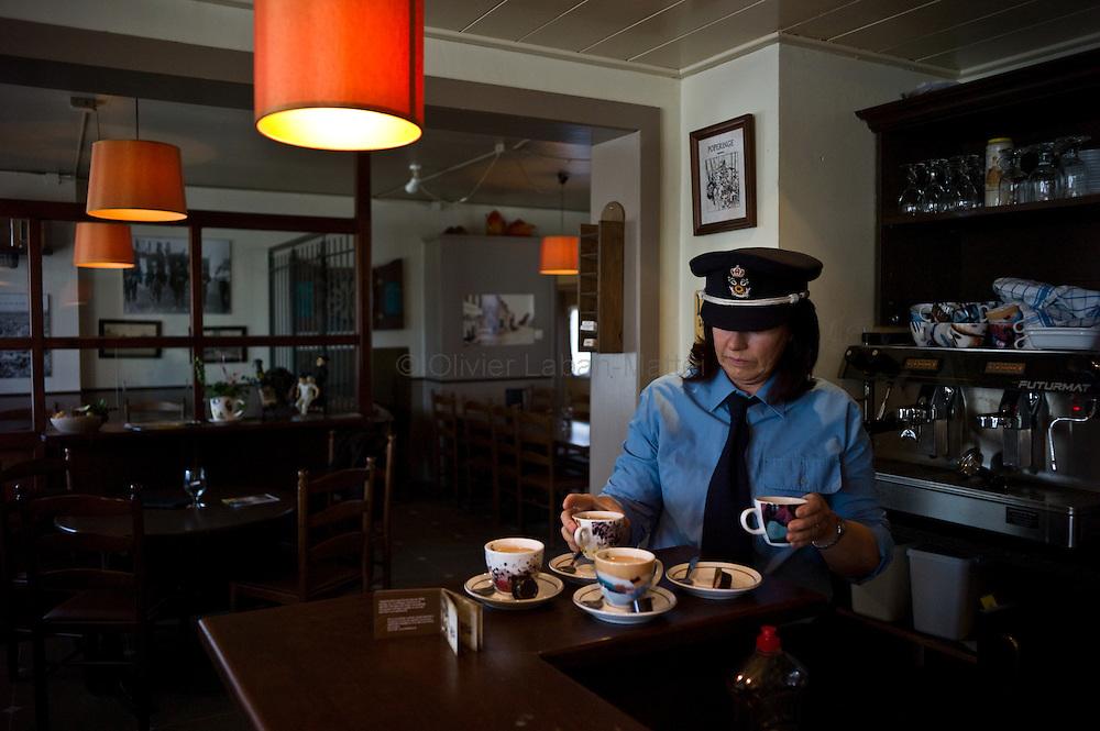 Le 23 octobre 2011, frontière Belgique / France, village de Poperinge (B), RN38. Déguisée en douanière belge, Patty, la propriétaire de l'ancien poste frontière belge de Poperinge transformé en bar-hôtel-musée, sert des cafés à des visiteurs de passage.