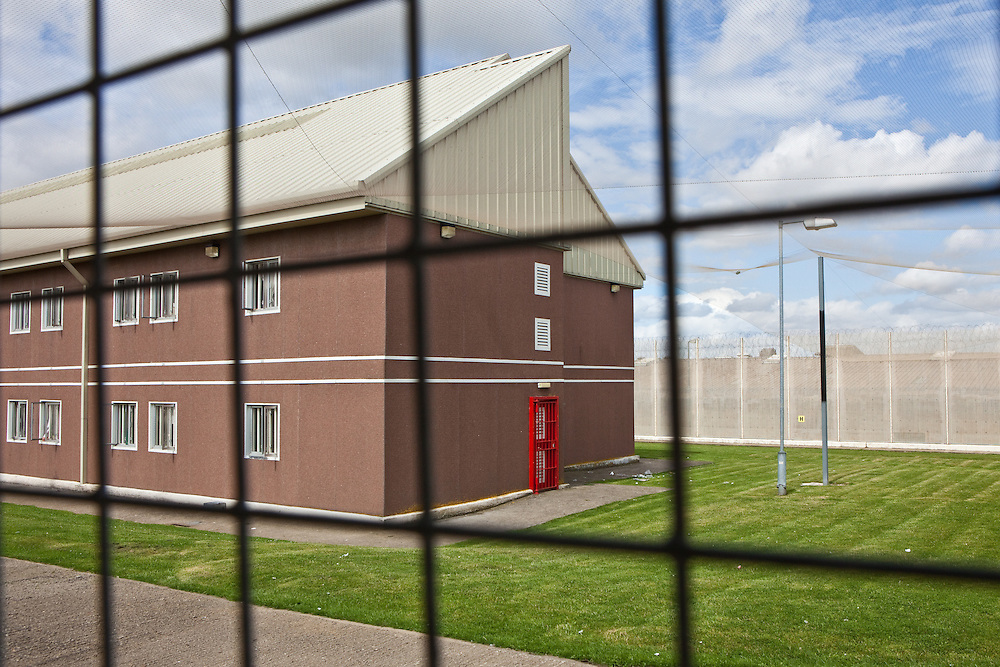 Ahigh security residential wing with anti-helicopter netting. HMP The Mount, Bovingdon, Hertfordshire