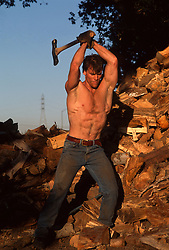 Shirtless muscular hunky man chopping firewood
