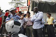 24 October 2007 - Guangzhou, China - An African man gets in to trouble with the police for a parking violation. By some estimates over 10,000 Africans from many different nations live and pass through Guangzhou which has overtaken Hong Kong as the new hub for African businessmen looking to cut out the middle man. Some come for a few weeks, others years. These African traders, most of whom come from West African nations like Ghana, Togo and Nigeria, profit by purchasing cheap goods direct from Chinese factories and then sending them back to their home countries where they can be sold at higher prices. Photo Credit: Luke Duggleby