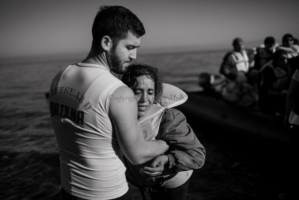 A man helps a woman as refugees and migrants riding a dinghy reach the shores of the Greek island of Lesbos after crossing the Aegean Sea from Turkey on November 13, 2015.